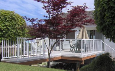 Classic deck featuring white picket railings and duradek vinyl decking membrane.