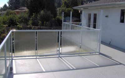 Deck featuring glass panel and white picket Railcraft railings and Duradek vinyl deck membrane.