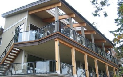 Large deck and patio project featuring glass panels flanked by pickets as well as Duradek vinyl decking.