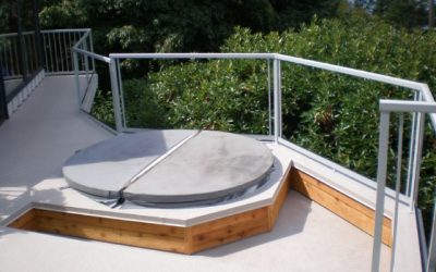 Deck with inset hot tub featuring glass panel Railcraft railings and Duradek vinyl deck membrane.